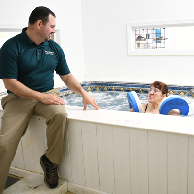 Therapist guides patient through aquatic therapy