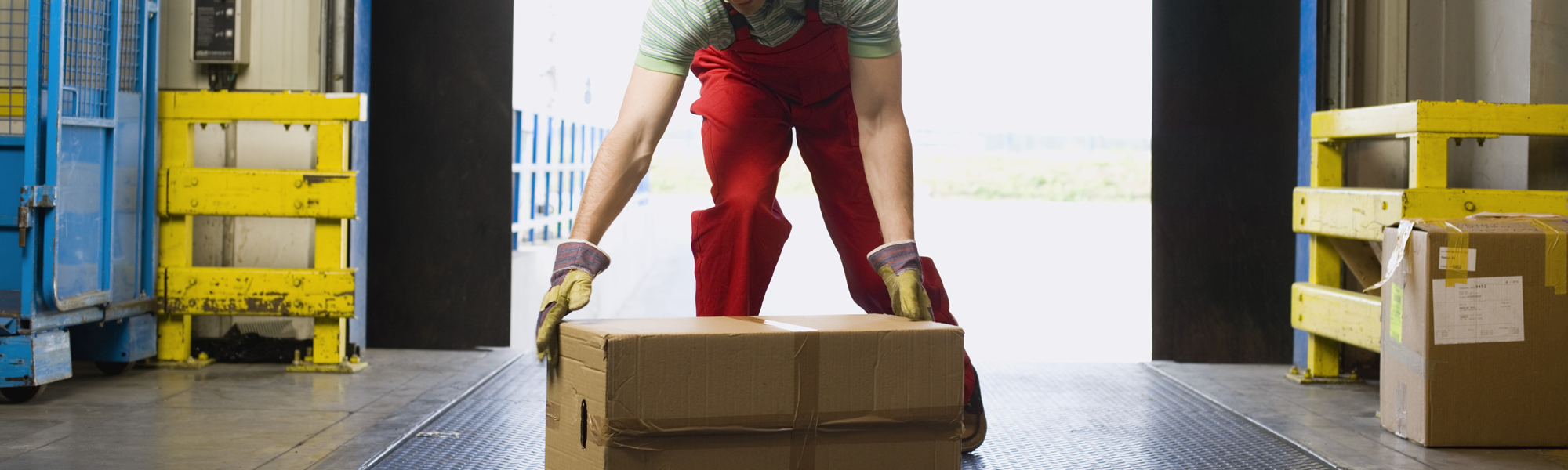 Worker preparing to lift box in warehouse